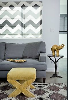 Interior designer Tamara Kaye-Honey has softened the textures and shapes of the mid century furnishings in this living Room. The larger grey diamonds in the geometric rug are outlined in plush silk pile. The yellow stool and blue grey sofa have rounded coners and the side table introduces an organic tree motif. Yellow and gold warm the cool grey and white color palette. Image courtesy House of Honey.