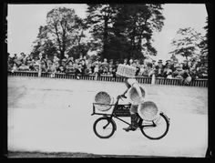 A photograph of a competitor at a charity sports day held at Herne Hill, London, taken in September 1938 by Sayers for the Daily Herald.    Competitors in the tradesmen's bicycle race had to carry half-bushel baskets as they cycled.