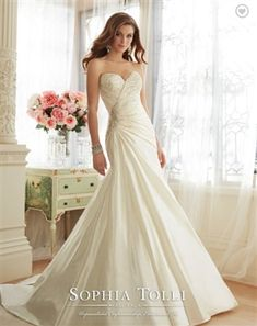 Strapless sweetheart dream taffeta fit and flare wedding dress, hand-beading highlights the asymmetrically draped bodice, sparkling beaded brooch on side, back corset, chapel length train. Removable spaghetti and halter straps included.