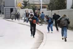 A Bosnian man cradles his child as they and others run past one of the worst spots for snipers that pedestrians have to pass in Sarajevo, on April 11, 1993. (AP Photo/Michael Stravato)