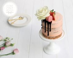 Semi-naked champagne and strawberry valentines or wedding cake with chocolate drip, macarons, gilded berries and rose.