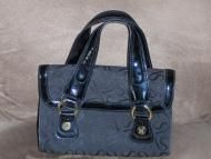 Price $21.97 Signature material of which I am not sure of what it is. I think to be cotton. Magnetic closure located under front flap of bag. Double p...