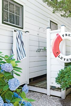 Make an outdoor shower stall feel more like an extension of the home by choosing materials and paint colors that blend in with the exterior, like the matching plank siding shown here. Wood floors add warmth and a nonslip surface for bare feet.