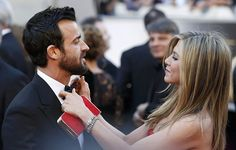 Jennifer Aniston ties up his fiancé Justin Theroux's bow tie at the Oscar's Academy Awards L.A. 2013