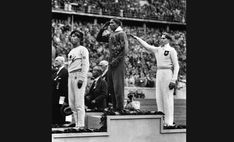 1936 Summer Olympics in Berlin - Jesse Owens, center, salutes during the presentation of his gold medal for the long jump on August 11, 1936