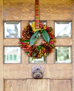 Add a splash of fall color to your front door with a leafy wreath. The plaid hanging ribbon means you can leave this wreath up until Christmas! #falldecor #fallideas #wreathideas #fallwreath #wreath #bhg