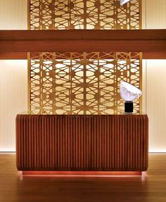 Reception Desk: Varnished Wood | The reception desk here features an emphasis on strong horizontal lines with thin strips of timber glued onto a marble or metallic surface.