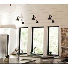 Kitchen Lighting Remodel Black window frames library lights, lots of white, brick or stone, open shelving. - I first fell in love with these library-style wall lights in an issue of Domino, which featured the bathroom (shown above) of editor Rita Konig Black Window Trims, Black Windows, Living Room White, White Rooms, Living Rooms, Kitchen Sink Window, Kitchen Windows, Kitchen Cabinets, Gray Cabinets