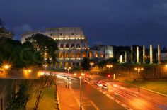 Famous roman Coliseum and illuminated streets of Rome at night