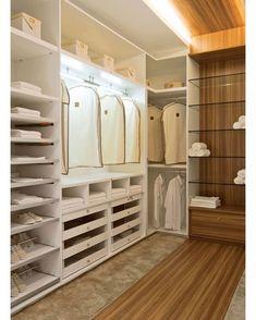 Closet aberto com iluminação interna. A paginação do piso inclui um detalhe de madeira que se extende até o teto.
