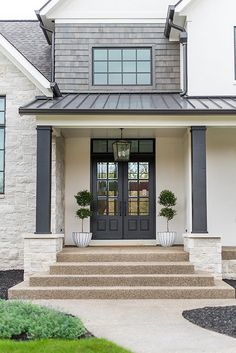 Black painted front door + patina cedar shingles + stone pillars | Whittney Parkinson Design