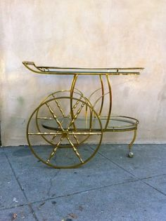 Vintage bar cart rolls on big wheels. Gold finish frame, two shelves and a front pivot caster to stabilize.