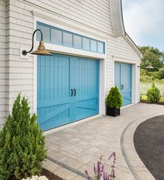 Carriage house garage doors by Clopay and two-tone pavers by Unilock make a grand statement.