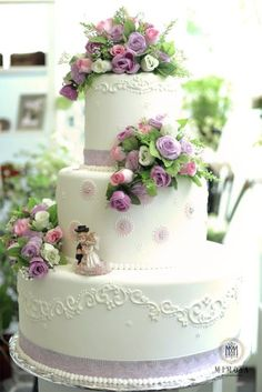 Beautiful white & purple cake......different flowers or feathers but maybe the crystal bride and groom that Daria gave would look really nice