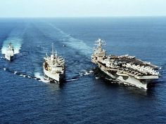 Operation Enduring Freedom, Nov. 24, 2001 — The fast combat support ship USS Sacramento (AOE-1) is in the process of replenishing the nuclear-powered aircraft carrier USS Theodore Roosevelt (CVN-71) as the guided missile cruiser USS Vella Gulf (CG-72) approaches her station alongside the AOE. Note a CH-46 Sea Knight helicopter, assigned to Sacramento, also carrying supplies to Theodore Roosevelt. U.S. Navy photo by Photographer's Mate 2nd Class Bobby McRill (# 011124-N-5526M-002).