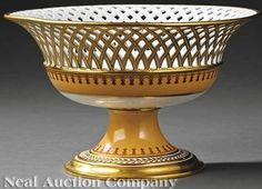 A Paris porcelain~Reticulated corbeille~Round form Ochre with crimson garlands on white ground~Gilt foot and accents~Origin France~Circa 1840-1880