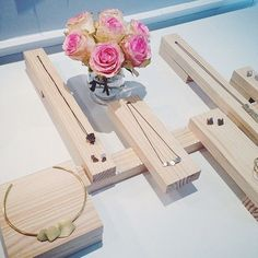 wooden blocks of different sizes to display jewelry - leaving some open/white space on table
