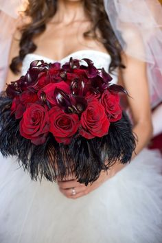 """bridal bouquet created with deep red roses and black feathers (I would use the """"draping red moss"""" instead of the feathers"""