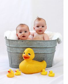 Sweet looking twins in metal bucket.