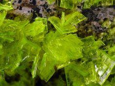 Autunite (hydrated calcium uranyl phosphate) with formula: Ca(UO2)2(PO4) 10-12H2O is a yellow - greenish fluorescent mineral with a hardness of 2 - 2½. Autunite crystallizes in the orthorhombic system and often occurs as tabular square crystals. Senhora da Assunção Mine, Aldeia Nova, Ferreira de Aves, Sátão, Viseu, Portugal  Dimensions: FOV 0.8 cm. Cesar M. Salvan