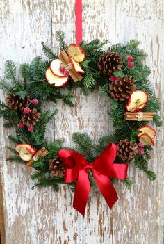 Traditional, Red Berry Wreath: A seasonal, spruce wreath filled with apple slices, bundles of cinnamon sticks, red berries and pine cones, perfectly finished off with a satin red ribbon bow and trailing ivy