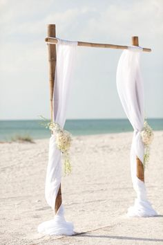 simple bamboo white wedding arch on the beach