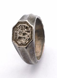 "Signet Ring: ca. 15thC, English, silver ""wreathed hoop with channelled shoulders; octagonal bezel engraved with stag within cabled border; inscription."" Has Gothic inscription meaning ""Henricus Souch."""