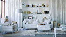 """Helles, freundliches Wohnzimmer bestehend aus KARLSTAD 3er-Sofa und KARLSTAD Hockern mit Bezug """"Blekinge"""" in Weiß, SIGURD Bank in Weiß, langflorigem HAMPEN Teppich in Weiß und langflorigem ÅDUM Teppich in Elfenbeinweiß, IKEA PS 2012 Couchtisch in Weiß und RITVA Gardinenschals mit Raffhaltern in Weiß"""
