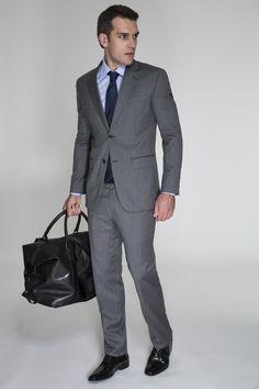 Costume cinza em padrão xadrez delicado, camisa azul e gravata marinho. A mala preta é perfeita para viagens rápidas.