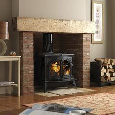 Earthy tones, red brick, wood mantel and a traditional stove. Sometimes you can't beat the classics. Earthy tones, red brick, wood mantel and a traditional stove. Wood Burner Fireplace, Inglenook Fireplace, Fireplace Hearth, Wood Stove Wall, Exposed Brick Fireplaces, Wood Stove Hearth, Craftsman Fireplace, Simple Fireplace, Wood Stove Surround