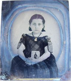 A heart string tugging Victorian photograph of a young girl in a mourning dress holding a photo of her father as a cavalryman, 1860s