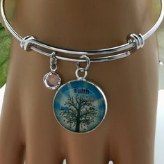 My new favorite bangle bracelet.  Bracelet comes in two sizes and has a smooth rhodium finish that does not tarnish. Tree of life with birds in the charm has a real mustard seed set in jewelers grade resin along with a Swarovski crystal set in rhodium. Only $20
