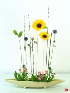 鬱陶しい梅雨が続いていますが、そんな中、植物は着実に成長しています。   梅雨が明けたら、誰が一番太陽に近いか競争だ!  下にいるのは、ミニバラ応援団   花型:自由花 花材:ヒマワリ、シマフトイ、ルリ玉アザミ、ミニバラ、ナルコユリ