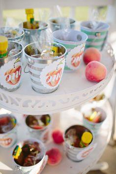Peach themed birthday party favors in mini tin buckets.