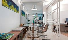 O espelho dá sensação de profundidade e amplia o espaço. Para não pesar no ambiente, o morador escolheu uma mesa com tampo de vidro e base de madeira em cruz. Seguindo a proposta de leveza, as cadeiras são de acrílico incolor e preto. Projeto de Daniel Tesser.