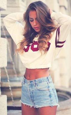 Hot outfit. Jersey cropped sweatshirt with high waisted distressed jean shorts