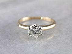 This engagement ring is simple and traditional, with a gently tapered shank and shoulders, and angular 6 prong head. What sets it apart from other classic style solitaires is the quality of the materials used. The head is bright white gold, the shoulders, and mounting 14k yellow gold. And at the center? A gorgeous, sparkling brilliant round cut diamond with excellent color and clarity. Perfectly elegant and sophisticated, this will pair nicely with a simple gold wedding ring, or with an…