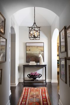 """This hallway off the main landing, which leads to the master bedroom and dressing room, could easily have been left empty. But Burnham saw an opportunity for a gallery-wall display of the couple's cherished family photos. """"Once we did that, the space grew in importance,"""" she says. So she built on the idea, adding a vintage rug and creating a vignette on a console table at the end of the hall."""