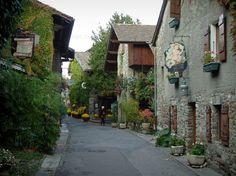 Yvoire: Rue fleurie du village médiéval avec maisons aux façades ornées d'enseignes, pots de fleurs et plantes grimpantes - France-Voyage.com