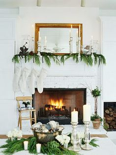 Yule style!! Noel Christmas!! Modern white fireplace and mantel in simple green garland and white candles! Love the gold mirror on the mantel too! Plus look at the dining table! Again - simple silver Christmas ornament balls in a silver bowl with pine stems! And white candles!! Always keep extra white candles in your pantry!