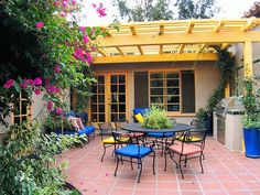 Designer's Notes Color is important in creating a Spanish-inspired dining area. The ochre pergola, Talavera tile behind the grill, Saltillo tile and cobalt blue seat cushions all work to enliven this festive outdoor room.
