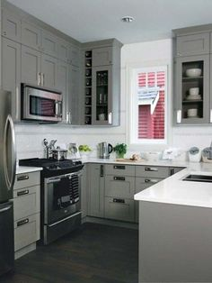 This compact kitchen with walls covered in to-the-ceiling cabinets, painted a mid-tone gray) is kept from feeling drab by the uncovered window, the white countertops & white backsplash that stretches all the way to the ceiling.  u-shaped-kitchen-19
