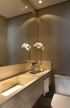 A cuba esculpida do lavabo, em mármore travertino romano bruto, é valorizada pelo papel de parede da #Papercom e pelo espelho iluminado que da amplitude ao ambiente.
