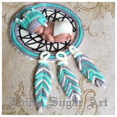 "Native American tribal theme cake topper 1 fondant baby 2 1/2"" long in diaper and headdress dream catcher base 4"" and feathers 2"" More"