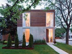 A cast-in-place concrete system forms the walls of the first floor and garden, while wood siding clads the upper level.