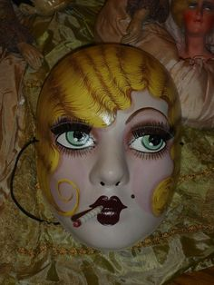 This Vintage Style Blonde Smoking Flapper Mask was made by flapperdashery on the Etsy community. It features a removable cigarette and has an elastic band for security. It is hand painted papier mache and its siblings are available in a great number of hair and eye colours.