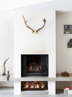this raised fireplace solves the problem of a convenient and stylish place to store fuel
