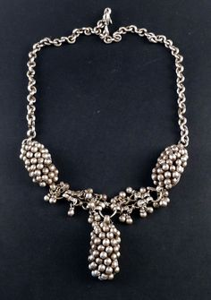 """This is a very special old necklace from Rajasthan. It was probably a forehead adornment converted into a necklace recently. The content of silver is very high. The 3 big pieces of the necklace were handmade using a traditional decorative technique called """"goli"""" , small hollow silver balls which are not welded to the base, but attached with a wire, giving them some slight movement. There are also some old and small silver dangles hanging from the chain."""