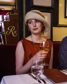 Lady Edith with simple, understated, long gold chain and gold drop earrings.