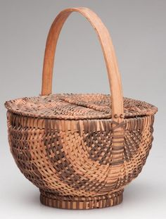 """CHEROKEE RIB-TYPE WOVEN SPLINT DOUBLE-LIDDED BASKET, white oak, finely woven melon form with a wrapped rim and opposing demilune-form lids hinged through the arched handle, the whole raised on an applied circular foot. Original dry natural surface with good dyed colors. $1.00 penciled on side of handle. Probably Western North Carolina. First half 20th century. 11 1/2"""" HOA, 6"""" H rim, 9"""" D rim."""